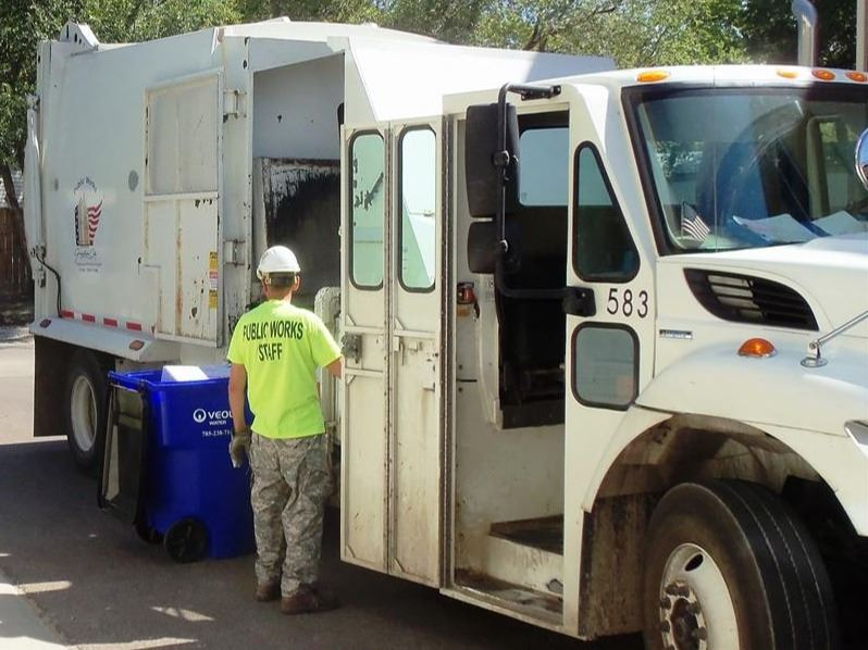 Public Works Staff Member Picking Up Curbside Garbage